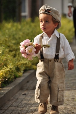 Little blonde boy in suspenders bringing a girl some flowers